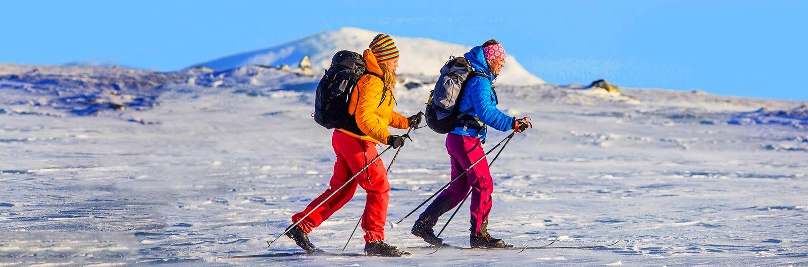 Couple ski touring in the sun